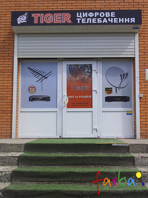 Брендування вхідної групи магазину в корпоративний стиль. На вікна поклеєна самоклеюча плівка з кольоровим друком, на якій знаходиться інформація для клієнтів, зверху знаходиться вивіска з назвою закладу.