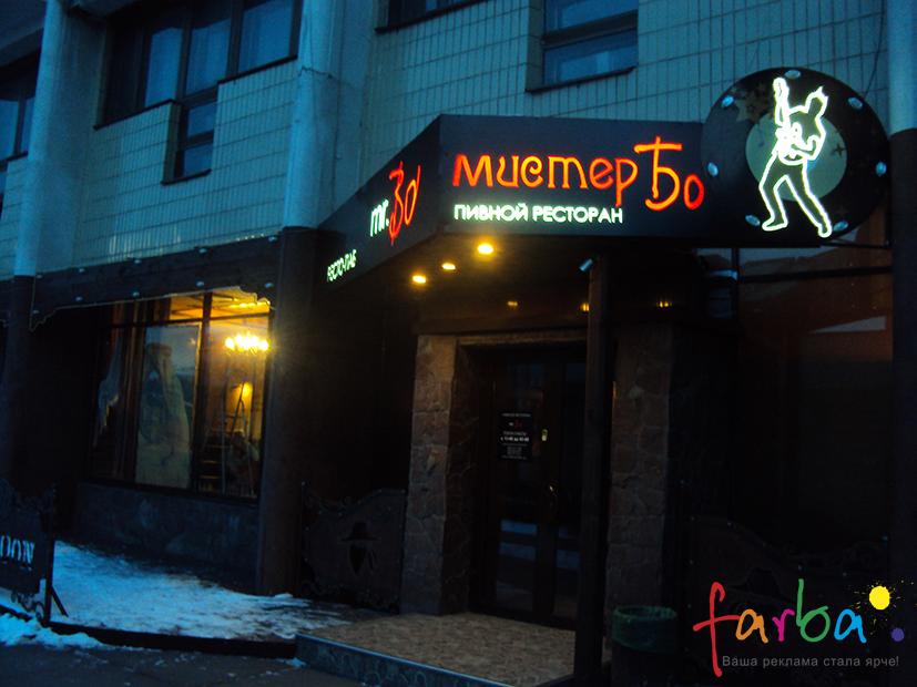 Композитний короб з світловими літерами і об'єктами, закріплений під кутом на вхідній групі пивного ресторану.