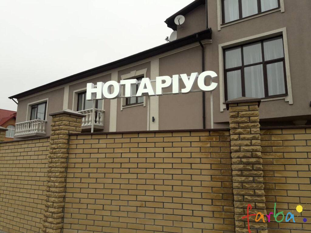 Пластикові світлові об'ємні букви, змонтовані на паркан будинку за допомогою металевої рами.