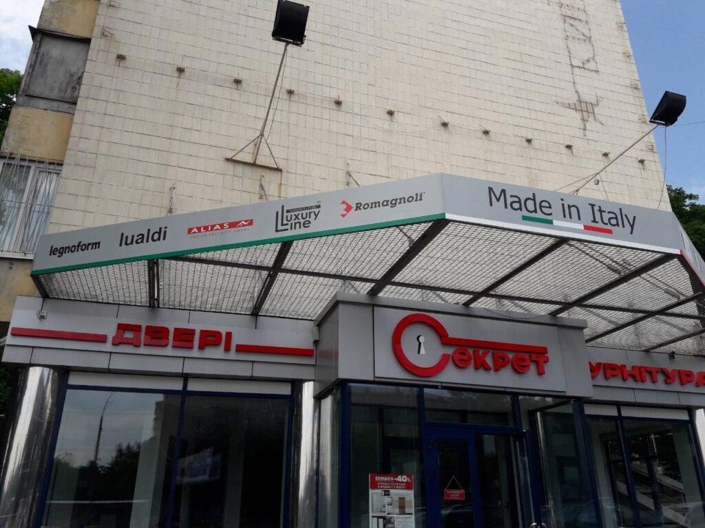 Зовнішні рекламні вивіски, розташовані на фасаді магазину дверей, що складаються з об'ємних світлових букв, розташованих на композитних основах, та трьох табличок, що виготовлені з пластику.