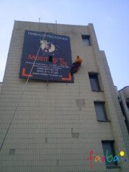Монтаж промисловими альпіністами конструкції з банером на стіну будівлі.