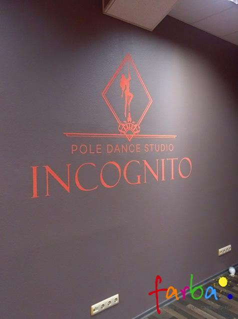 Логотип та назва компанії, нанесена на фарбовану стіну фарбою іншого кольору через одноразовий трафарет з самоклеючої плівки.