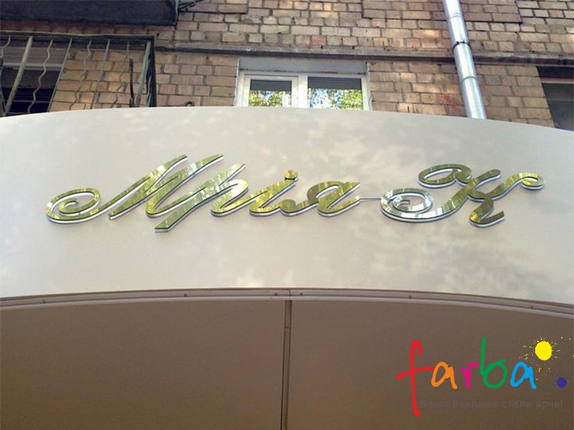 Об'ємні букви на композитній основі, виготовлені з двох шарів акрилу різного кольору, змонтовані на піддашок будинку.