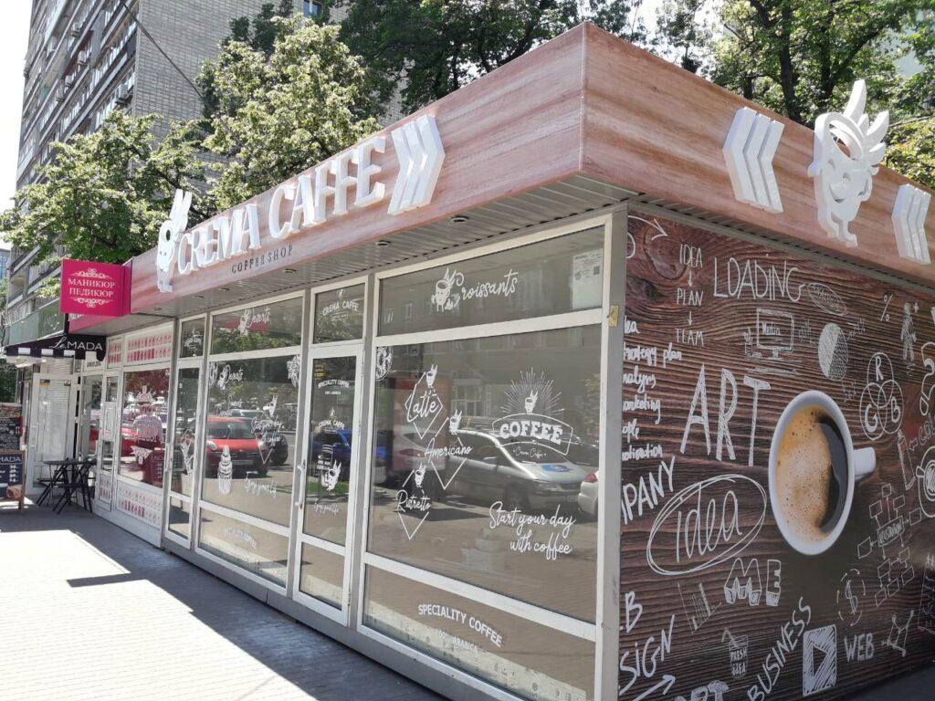 Зовнішня реклама на кіоску з продажу кави, що включає в себе об'ємні світлові букви з логотипом, композитний фриз та наклейки на вікна. Букви мають внутрішнє підсвічування, фриз має зображення, яке копіює дерев'яну поверхність, наклейки виготовлені з білої плівки і нанесені на скло.