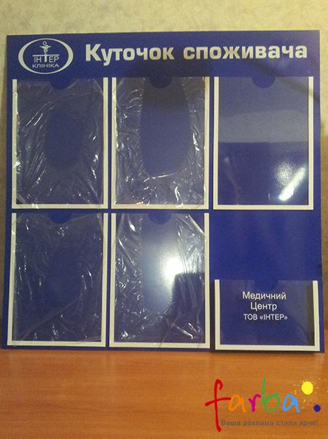 Куточок споживача в вигляді пластикового стенду з п'ятьма карманами для аркушів формату А4 та одним для книги скарг та пропозицій.