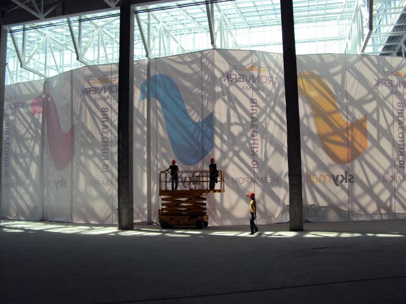 Монтаж завіси з банерів для зонування простору в торговому центрі. Для даного виду монтажу використовується підіймальна техніка.