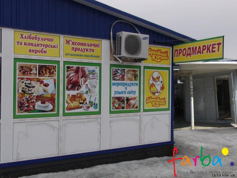 Реклама на фасаді магазину продуктових товарів, виконана з використанням кольорових наклейок на вікна та виносної двосторонньої вивіски з металевою рамкою.