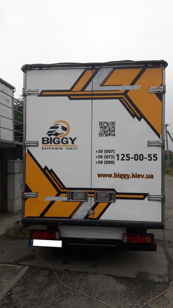 Задні двері будки вантажного автомобіля, на які нанесена самоклеюча плівка з рекламою.