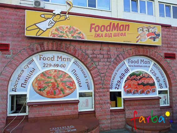 Оформлення фасаду магазина з доставки їжі. На вікна нанесені наклейки з тематичними зображеннями та, потрібною для клієнтів, інформацією, зверху прикріплений світловий короб з елементами, які винесені за межі основи.