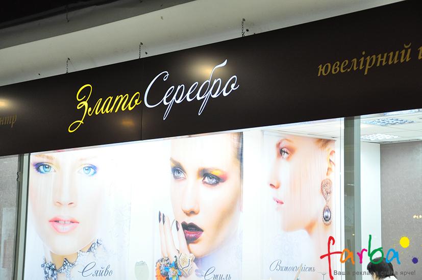 Композитний короб з світловими буквами посередині, закріплений над входом в магазин на декоративні ланцюги.