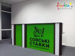 Наклейка чорного кольору, виготовлена за допомогою плотерної порізки і поклеєна на площину зеленого кольору всередині приміщення.